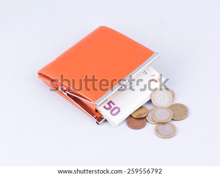 orange purse with fifty euro and coins isolated on white cloth - stock photo