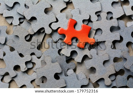 Orange puzzle pice standing out from larger group puzzle pieces. Business concept - branding, different, original. - stock photo