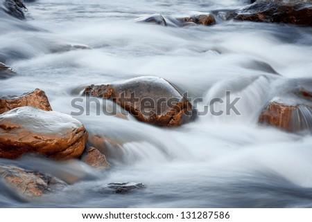 orange rocks in the river water - stock photo