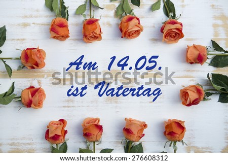 orange roses on wood with german text: Am 14.05. ist Vatertag (fathers day is on 14.05.) - stock photo