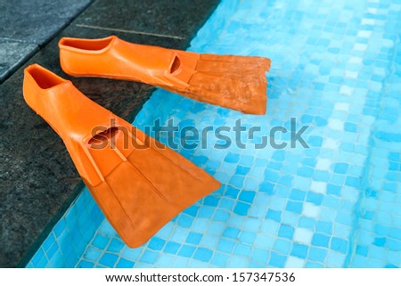 Orange Rubber flippers on the side of the swimming pool - stock photo