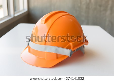 orange safety helmet hard hat, tool protect worker of danger in construction industry - stock photo