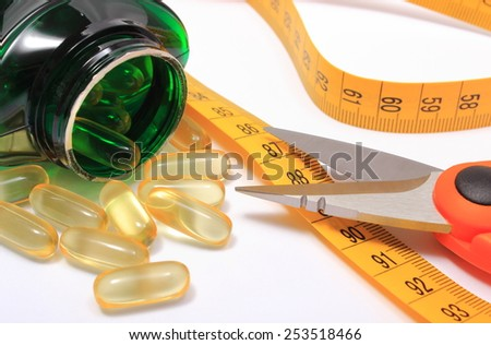 Orange scissors with tape measure and slimming pills poured from bottle on white background, concept for slimming - stock photo
