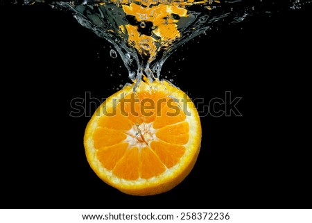 orange sinking into water on black - stock photo