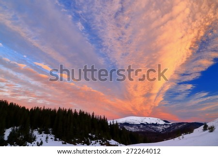 Orange sky cover distant mountains in early winter morning - stock photo