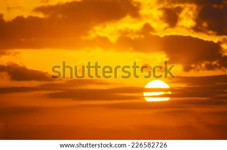 orange sky with a shining sun at sunset - stock photo