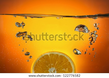 Orange slice dropped in water - stock photo