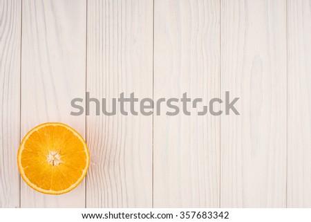 orange slice on white wooden table , top view - stock photo