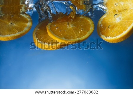 Orange slices dropped in crystal clear water with blue gradient background - stock photo