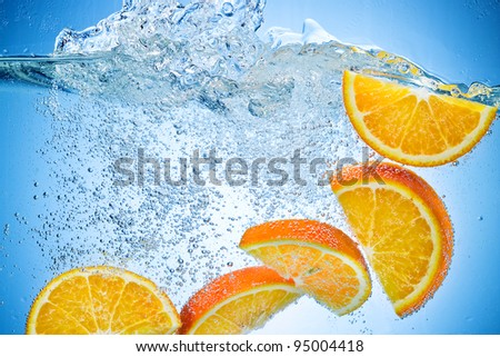 Orange Slices falling deeply under water with a big splash on blue background - stock photo