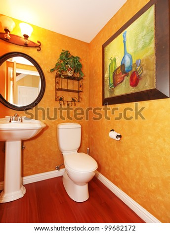 Orange small bathroom with large painting. - stock photo