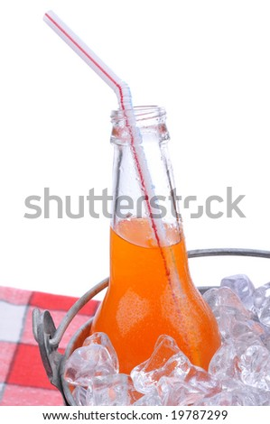 Orange soda bottle in bucket of ice on checkered table cloth isolated on white - stock photo