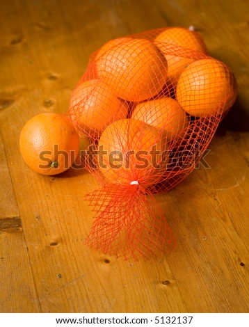 Orange spilled from the bag onto kitchen table - stock photo