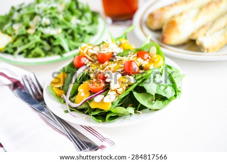 Orange spinach salad on the plate in Italian restaurant.