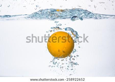 orange splash in water  - stock photo