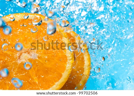 Orange splash in water, top view, bubbles with fruit reflection - stock photo