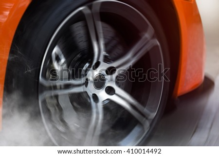 Orange Sport Car with detail on spinning and smoking wheels/tires doing burnouts, dynamic photo - stock photo