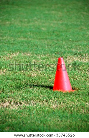 orange sports cone on grass background with blurred fore and background.