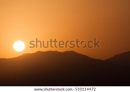 Orange sunrise on the background of mountains. Nature background