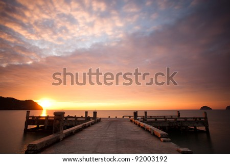 Orange sunset and cloudscape over sea with pier in foreground. - stock photo