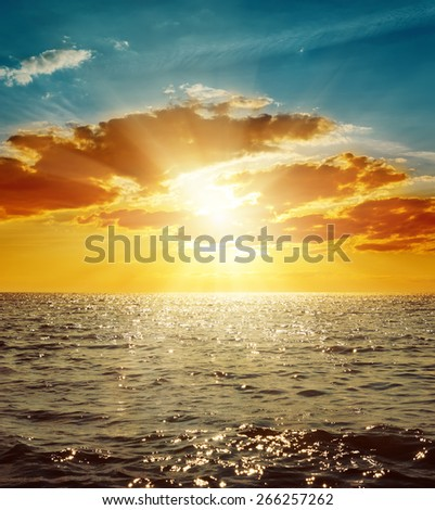orange sunset in clouds over sea - stock photo