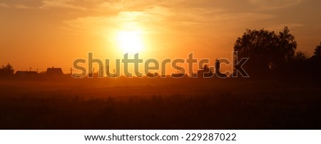 Orange sunset in the countryside. Russian village. - stock photo