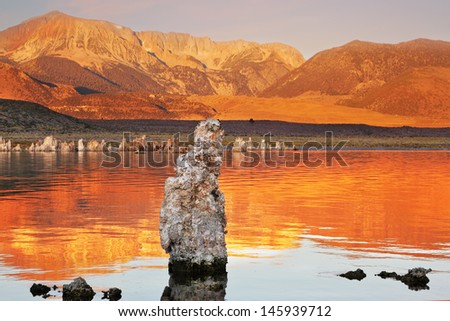 Orange sunset. The magic of Mono Lake. Outliers - calcareous tufa formation  on the smooth water of the lake - stock photo