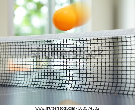 Orange table tennis ball moving over net on blue table - stock photo