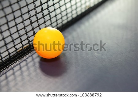 Orange table tennis ball on blue table with net - stock photo