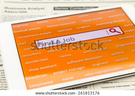 """Orange tablet screen fill with difference career words.  Internet website for online job search having wording """"find a job"""" and searching symbol in search engine box. Blur classifieds on background. - stock photo"""