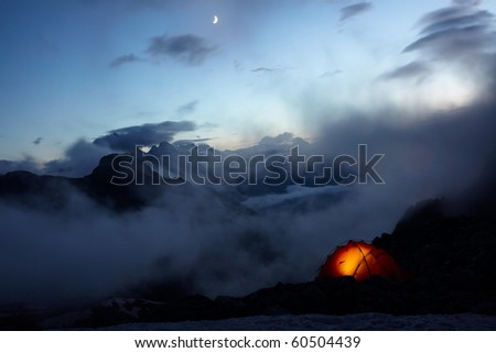 Orange tene in the mountains and moon on the sky - stock photo
