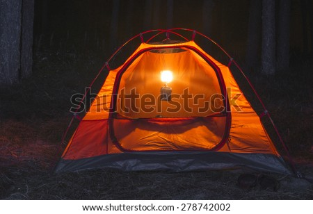 Orange tent in the forest at night - stock photo