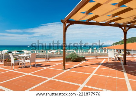 orange tiled terrace with desk and chairs with shadow roof at blue sea - stock photo