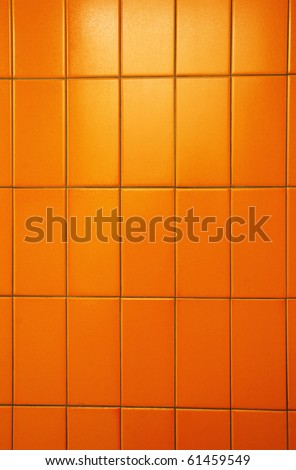Orange tiles of a public bathroom wall. Great color and tiles also have orange peel texture. - stock photo
