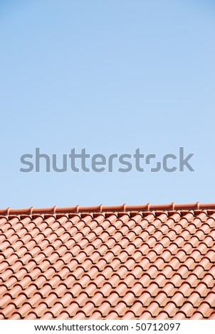 orange tiles on the roof of a house against blue sky background
