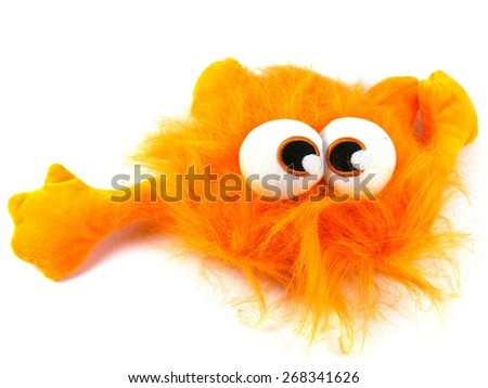Orange toy monster with long hair and bulging eyes as a soccer mascot over white - stock photo