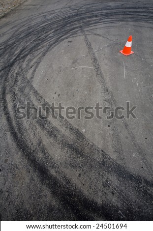 Orange traffic cone and round car drift skid marks - stock photo