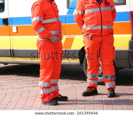 Orange uniforms of the paramedics for emergency rescue and an ambulance - stock photo