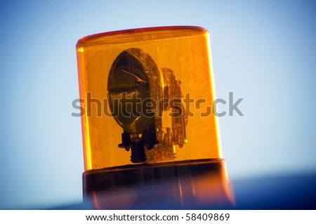 Orange warning light atop a car's roof against a blue sky - stock photo