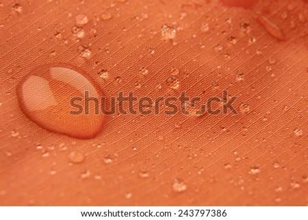 Orange waterproof coating background with water drops - stock photo