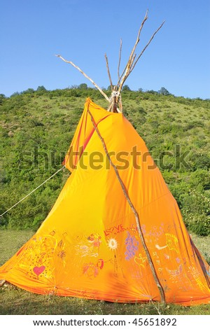 Orange wigwam with hippy drawings against green hill and blue sky, selective focus - stock photo