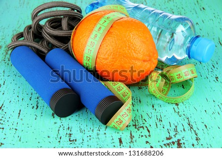 Orange with measuring tape,skipping rope and bottle of water, on color wooden background - stock photo