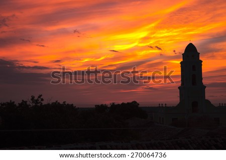 Orange, yellow, pink sunset rooftop view over Trinidad, Cuba - stock photo