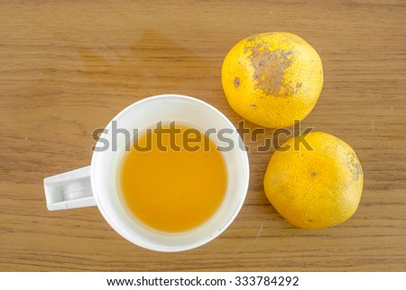 Oranges and a cup of orange juice on wooden table - stock photo