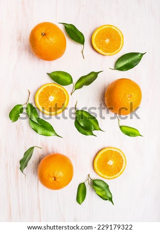 Oranges fruits composition with green leaves and slice on white wooden background, top view - stock photo