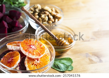 Oranges, honey, beetroot, walnuts and mint leaves on table. - stock photo