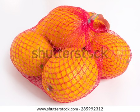 Oranges in red netting isolated on white