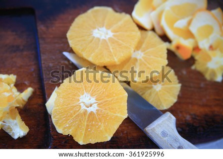Oranges peeled and cut into rounds with knife on cutting board - stock photo