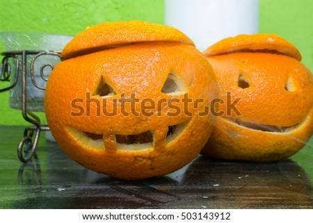 oranges with carved faces with white candles  on a green background with the autumn Halloween theme
