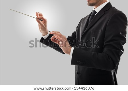 Orchestra conductor directing with his baton - stock photo